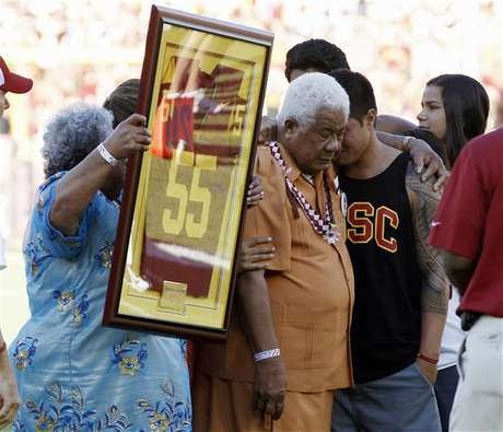 Family members hold up a No. 55 jersey as part of a ceremony held in memory of the late former USC Trojans, San Diego Chargers and NFL linebacker Junior Seau after the first quarter of the NCAA football game between the USC Trojans and the Hawaii Warriors in Los Angeles September 1, 2012.