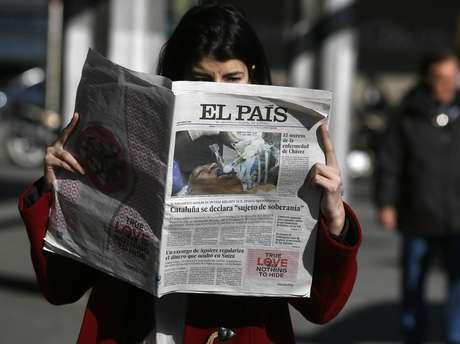 Mulher lê a versão do 'El País' impressa com a foto falsa de Hugo Chávez no centro de Madri, na Espanha