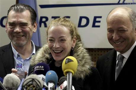 Florence Cassez reacts next to her lawyer Frank Berton (L) and French Foreign Minister Laurent Fabius (R) during a news conference after her arrival at Charles de Gaulle Airport in Roissy, near Paris January 24, 2013.