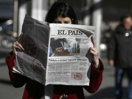 "A woman poses with a copy of the January 24 first edition of Spanish newspaper El Pais in central Madrid January 24, 2013. Spain's influential El Pais newspaper withdrew what it said was ""false photo of Hugo Chavez"" that it had published in its on-line and print editions on Thursday."