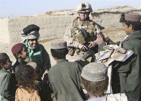 2nd Lt. Carly E. Towers (R), the officer in charge of the female engagement team, 2nd Battalion, 2nd Marine Regiment, and Sahima Sheren, or Sam, an interpreter with the FET team, interact with children during a patrol through Tajik Khar in Garmsir, Afghanistan, in this December 18, 2009 U.S. Marine Corp handout photo.