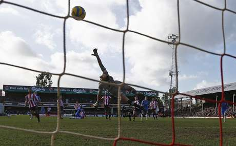 Fernando Torres (3rd R) shoots and scores past Brentford goalkeeper Simon Moore to equalize 2-2.