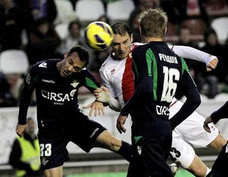 El delantero serbio del Rayo Vallecano Andrija Delibasic (c) remata de cabeza para marcar gol, segundo para el conjunto madrileño, ante los jugadores del Real Betis, Nacho Pérez (i) y Perquis (d), durante el partido de la vigésimo primera jornada de Liga de Primera División disputado esta tarde en el Estadio de Vallecas.