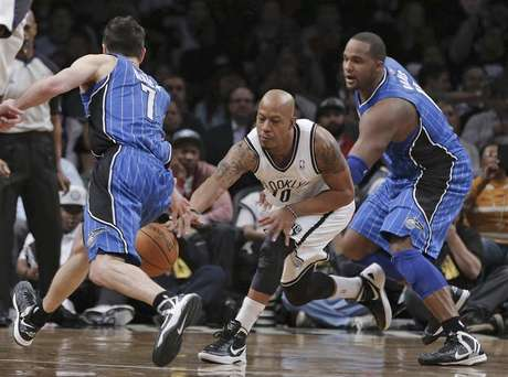Brooklyn Nets forward Keith Bogans (10) cuts between Orlando Magic guard J.J. Redick (7) and forward Glen Davis (11) to steal the ball in the fourth quarter of their NBA basketball game in New York, January 28, 2013.