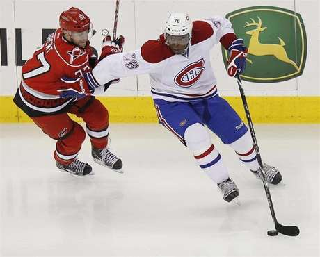 The Montreal Canadiens' P.K. Subban (R) battles the Carolina Hurricanes' Tim Brent for the puck during their NHL hockey game in Raleigh, North Carolina April 5, 2012.
