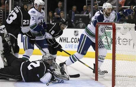 Vancouver Canucks' Zack Kassian (R) scores past Los Angeles Kings goaltender Jonathan Quick (bottom) during the first period of their NHL game in Los Angeles, California, January 28, 2013.