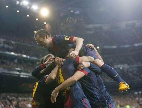 Barcelona's Andres Iniesta (top) and teammates celebrate Cesc Fabregas' goal.