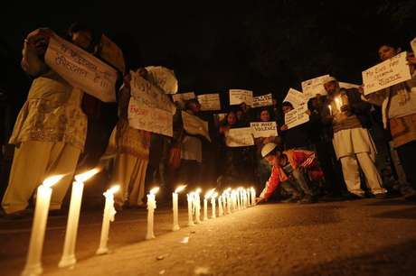 A boy places a candle as demonstrators hold placards during a candlelight march for a gang rape victim, who was assaulted in New Delhi in this file photo taken January 16, 2013.