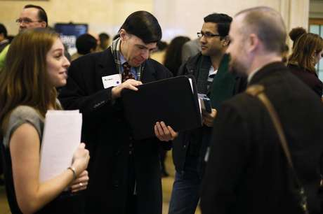 A man looks for a copy of his resume to give to a recruiter at a job fair put on by online recruiting company TheLadders at Grand Central Station in New York, January 10, 2013.