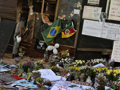 Policial observa o interior da Boate Kiss, cuja fachada foi coberta por homenagens às vítimas do incêndio