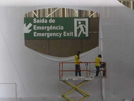 Trabalhadores rasgam tecido que escondia placa indicando saída de emergência no Anhembi Parque