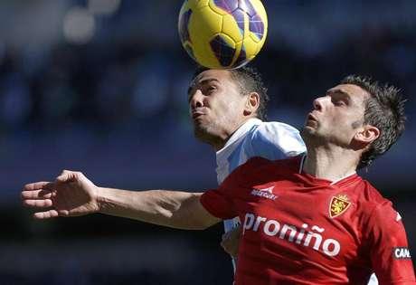 El defensa brasileño del Málaga Weligton Robson Pena de Oliveira (i) lucha por el balón con el delantero portugués del Real Zaragoza Hélder Manuel Marques Postiga, durante el partido de la décimosegunda jornada de la Liga de Primera División, que ambos equipos disputan este mediodía, en el estadio de la Rosaleda en Málaga