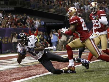 Baltimore Ravens wide receiver Jacoby Jones (12) dives into the end zone for a second quarter touchdown past San Francisco 49ers cornerback Tarell Brown (25) and defensive back Chris Culliver (29) in the NFL Super Bowl XLVII football game in New Orleans, Louisiana, February 3, 2013.