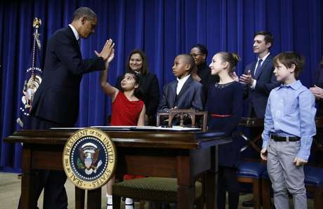 U.S. President Barack Obama high-fives eight-year-old Hinna Zejah after unveiling a series of gun control proposals during an event at the White House in Washington, January 16, 2013.