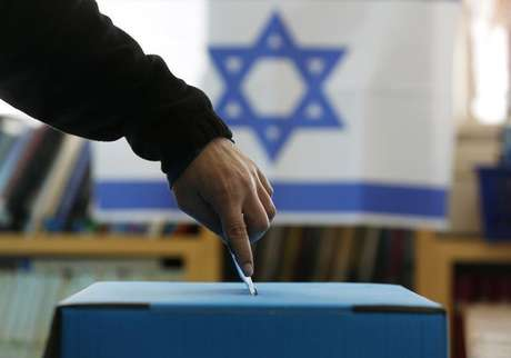 An Israeli flag is seen in the background as a man casts his ballot for the parliamentary election at a polling in the West Bank Jewish settlement of Ofra, north of Ramallah January 22, 2013.