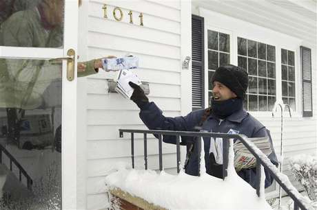 Mail carrier Mike Perkins delivers mail in the snow in Waterloo, Iowa in this file photo taken December 20, 2012.