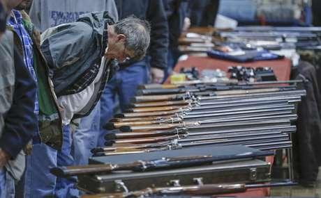 Un posible cliente observa escopetas durante una muestra de armas en el Centro de Convenciones Plaza Empire State en Albany, Nueva York, el 26 de enero de 2013. Cuatro senadores intentan alcanzar una solución negociada para ampliar el requisito sobre la verificación de los antecedentes a quienes quieran poseer un arma.