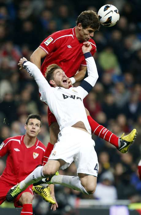 <p>Real Madrid's Sergio Ramos (bottom) and Sevilla's Federico Fazio challenge for the ball.</p>