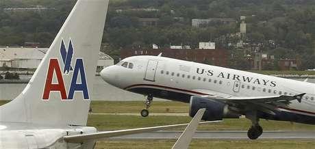 A US airways plane takes off behind an American Airlines jet at Ronald Reagan National Airport in Washington April 23, 2012.