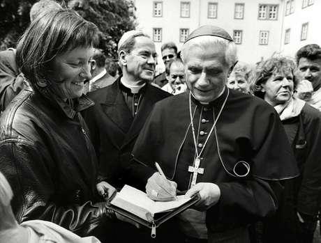 Em 1994, ratzinger já gozava de fama entre católicos. Nesta imagem, feita em junho, ele autografa uma publcação no aniversário de 1240 anos da cidade alemã de Fulda