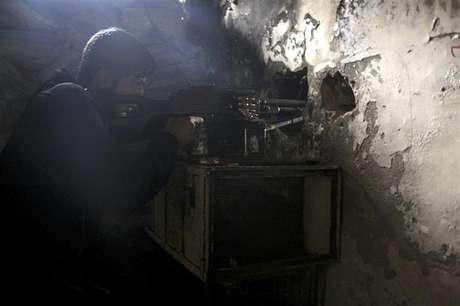 Un miembro del Ejército de Siria Libre apunta su arma a través de un agujero en una pared mientras toma una posición defensiva en Aleppo, feb 11 2013. Militantes opositores sirios capturaron un aeropuerto militar cercano a la ciudad de Alepo el martes, en otro revés para las fuerzas del presidente Bashar al-Assad, que han sufrido cada vez más ataques en todo el país.