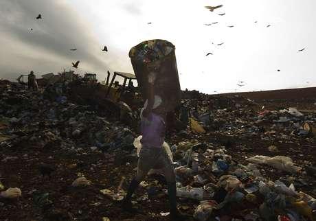 Mulher carrega lixo no Jardim Gramacho, maior aterro sanitário da América Latina: material esconde muito valor e é fonte matérias-primas, segundo especialistas