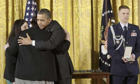 U.S. President Barack Obama (3rd L) hugs Sarah Davino (L) and Mary Davino (2nd L), as he awards the Presidential Citizens Medal posthumously to their family member Rachel Davino, a teacher who gave her life in the Sandy Hook school shooting in Connecticut in December, in the East Room at the White House in Washington, February 15, 2013.