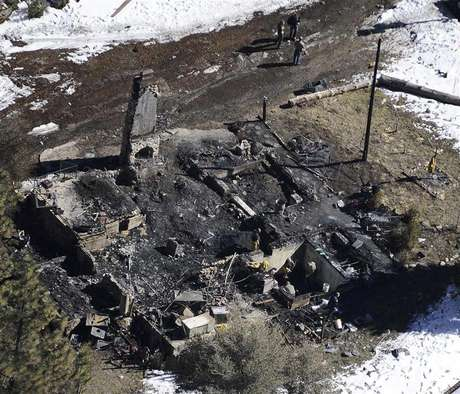 Authorities stand at the site of a burnt out cabin near Angelus Oaks, California February 13, 2013, where police believe they engaged in a shootout with fugitive former Los Angeles police officer Christopher Dorner on Tuesday.