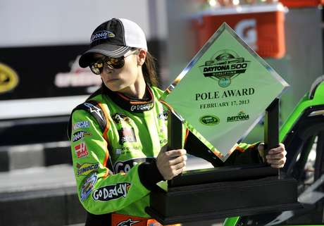 <p>NASCAR Sprint Cup Series driver Danica Patrick, of the number 10 car, picks up her trophy in victory lane as she celebrates securing the pole position for the upcoming Daytona 500, during qualifying for the Daytona 500, at Daytona International Speedway in Daytona Beach, Florida, February 17, 2013. </p>