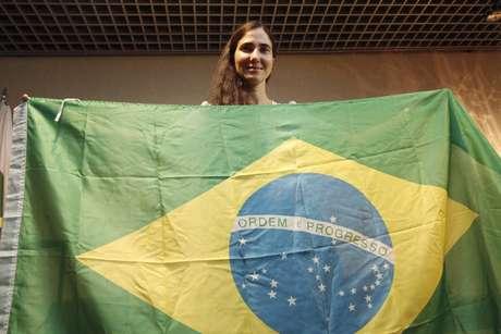 A blogueira dissidente cubana Yoani Sánchez posa com a bandeira brasileira após desembarcar no aeroporto de Guararapes, em Recife (PE)