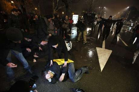Protesters lie on the ground after clashes with riot police during a protest against high electricity prices in Sofia February 19, 2013.