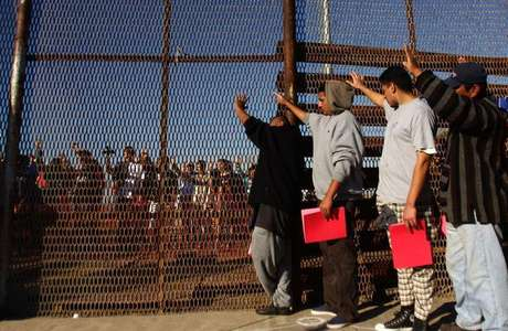 A group of recently deported immigrants stand near the double steel fence that separates San Diego and Tijuana at the border in Tijuana December 10, 2011.