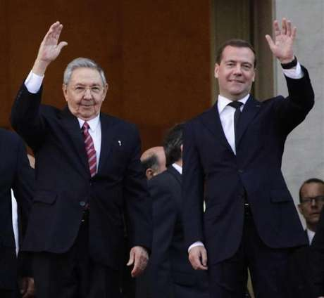 Russia's Prime Minister Dmitry Medvedev and Cuban President Raul Castro (L) wave at the entrance of the Revolution Palace in Havana, February 21, 2013.