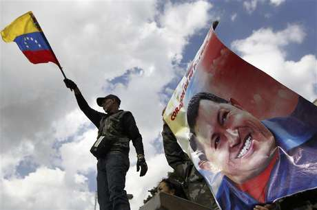 A supporter of Venezuela's President Hugo Chavez waves a national flag next to a giant picture of Chavez, in front of a military hospital where Chavez is being treated, in Caracas February 19, 2013.