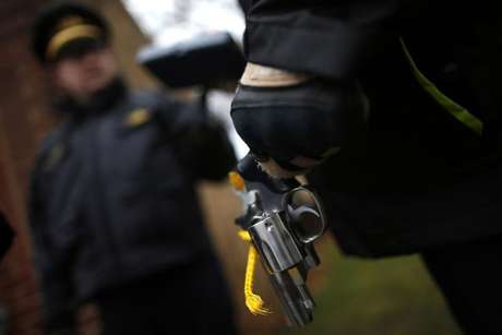 An Evanston police officer holds a firearm that was turned in as part of an amnesty-based gun buyback program in Evanston, Illinois December 15, 2012.