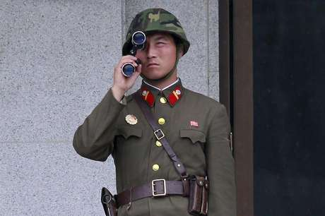 A North Korean soldier looks south through a pair of binoculars on the north side of the truce village of Panmunjom in the demilitarised zone separating the two Koreas in Paju, about 55 km (34 miles) north of Seoul, August 25, 2010.