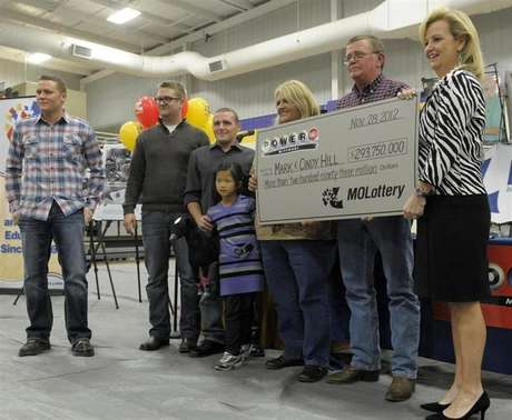 The Hill family holds an oversized check presented by Missouri Lottery director May Scheve (R) during a news conference at the North Platte High School in Dearborn, Missouri, November 30, 2012.