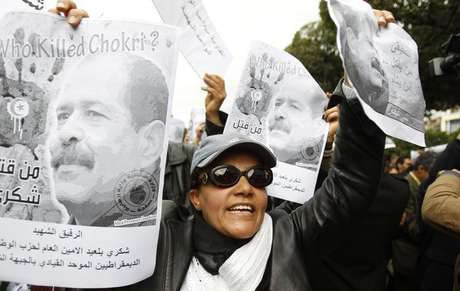 A woman chants slogans and holds pictures of assassinated leftist politician Chokri Belaid during a demonstration against the Islamist Ennahda movement in Tunis February 23, 2013.