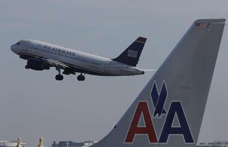 A U.S. Airways jet departs Washington's Reagan National Airport next to an American Airlines jet outside Washington, February 25, 2013.