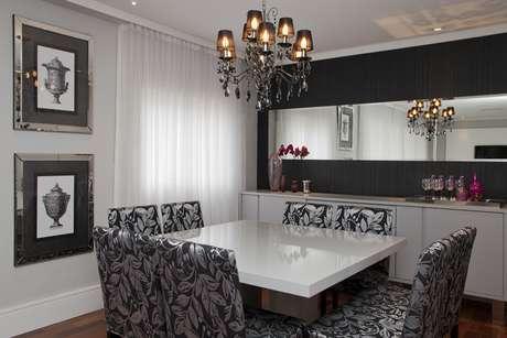 Na sala de jantar, as cores preta e branca predominam. A mesa e o buffet brancos contrastam com as cadeiras estampadas