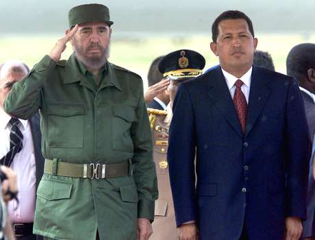 Presidente cubano Fidel Castro faz saudação durante a execução do hino nacional em sua primeira visita à Venezuela durante o governo Chávez, em 26 de outubro de 2000