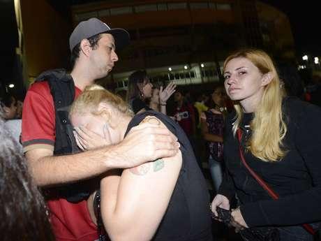 <p>Fãs da banda se consolam do lado de fora da Arena Santos</p>