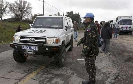 """Soldado filipino das forças de paz da ONU fica ao lado de veículo da ONU na passagem fronteiriça de Kuneitra, de Israel para a Síria, nas Colinas de Golã. Rebeldes que detêm 21 soldados da ONU perto das Colinas de Golã, no sul da Síria, disseram que as forças do governo devem deixar a área antes de libertar seus """"convidados"""", informou um ativista em contato com os combatentes. 05/03/2013"""