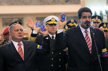 In this photo released by Miraflores Press Office, Venezuela's acting President Nicolas Maduro, right, the President of the National Assembly Disdado Cabello, left, and Defense Minister Adm. Diego Molero, center, hold up miniature copies of Venezuela's Constitution during a symbolic swearing in ceremony for Maduro in front of Venezuela's late President Hugo Chavez's coffin at the military academy where the funeral ceremony was held earlier, in Caracas, Venezuela, Friday, March 8, 2013. Chavez died on March 5 after a nearly two-year bout with cancer. Maduro was sworn in at the National Assembly earlier against the objections of the political opposition who said the move violated the country's constitution.