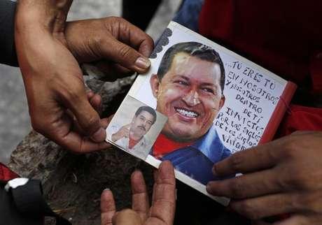 Partidário do presidente da Venezuela Hugo Chávez cola uma foto do presidente atuante Nicolás Maduro sobre uma foto de Chávez em Caracas, Venezuela. 11/03/2013