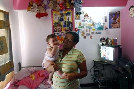 Marisol Aponte, 49 anos, posa para foto com o filho em sua casa