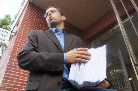 <p>Jader Marques, advogado de Elissandro Spohr, o Kiko, um dos donos da Kiss, sai da delegacia com cópias do processo</p>