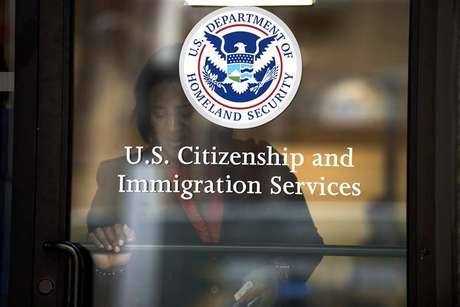 A woman leaves the U.S. Citizenship and Immigration Services offices in New York, in this August 15, 2012 file photo.