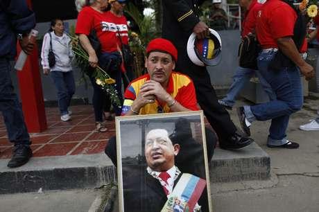 <p><strong>15 de março -</strong>Com foto de Chávez, seguidor aguarda para despedida final do falecido presidente</p>
