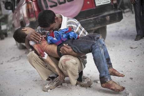 Pai chora segurando o corpo do filho, morto pelo Exército Livre da Síria, perto ao hospital Dar el-Shifa, em Aleppo